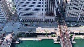 Tráfego na movimentação de Wacker e o St de LaSalle, os barcos no Chicago River e as cruzes do trem o EL da rua de Wells para seg filme