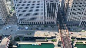 Tráfego na movimentação de Wacker, nos barcos entrados no Chicago River e nas cruzes do trem a trilha do EL da rua de Wells na vi video estoque