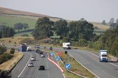 Tráfico de autopista con el carril cerrado para las obras viales Fotos de archivo
