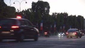 Tráfico de coche céntrico de París en el bulevar de Champs-Elysees en luz del crepúsculo