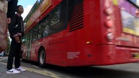 Tráfico de espera de movimiento lento, taxis y autobuses rojos de Londres del autobús de dos pisos conduciendo más allá de Selfri almacen de video