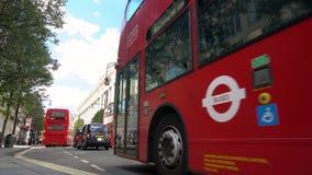 Tráfico de espera de movimiento lento, taxis y autobuses rojos de Londres del autobús de dos pisos conduciendo más allá de Selfri metrajes