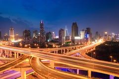 Tráfico de la carretera de la ciudad en anochecer Imagen de archivo libre de regalías