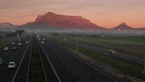 Tráfico de la carretera en Cape Town, con la montaña de la tabla en el fondo, temprano por la mañana almacen de metraje de vídeo