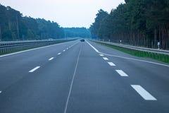 Tráfico de la carretera en puesta del sol con los coches y los camiones Fotografía de archivo