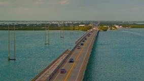 Tráfico de la carretera que conduce en un puente que cruza el océano metrajes