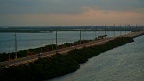 Tráfico de la carretera que conduce en un puente que cruza un océano almacen de metraje de vídeo