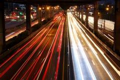 Tráfico de la velocidad - la luz se arrastra en el camino en la noche imagen de archivo libre de regalías