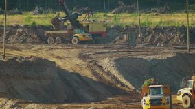 Tráfico de los camiones volquete de la explotación minera en el desarrollo de un hoyo de arena metrajes