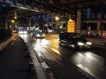 Tráfico de noche en las calles lluviosas Fotografía de archivo libre de regalías