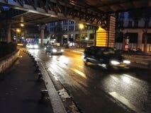 Tráfico de noche en las calles lluviosas Imágenes de archivo libres de regalías