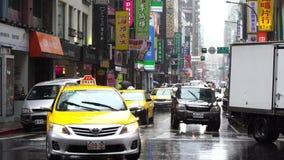 Tráfico en el camino con lluvia el caer en el distrito de Ximen, Taipei, Taiwán metrajes