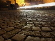 Tráfico en el camino del guijarro en la noche Imagen de archivo
