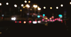Tráfico en fondo de la falta de definición de la ciudad de la noche Círculos móviles del bokeh del tráfico de la noche almacen de video