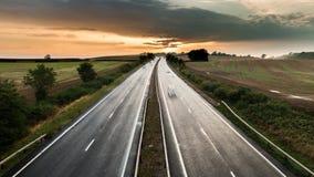 Tráfico en la autopista rural en la puesta del sol metrajes