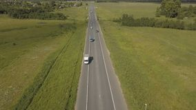 Tráfico por carretera de la carretera en un valle Lanzamiento aéreo de un camino de la carretera con los coches del tráfico en un almacen de metraje de vídeo