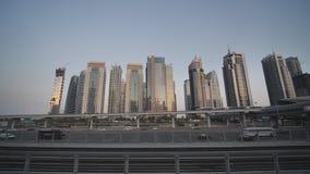 Tráfico por carretera en Dubai contra la perspectiva de casas durante crepúsculo almacen de metraje de vídeo