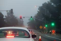 Tráfico que comienza en conos de la luz verde de la niebla Fotografía de archivo
