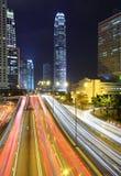 Tráfico a través en el centro de la ciudad en la noche Imagen de archivo