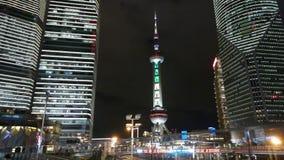 Tráfico urbano en la noche, el rascacielos de Shangai y la torre de la perla TV de Oriente almacen de video