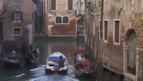 Tráfico y góndolas del barco en un pequeño canal en Venecia almacen de video