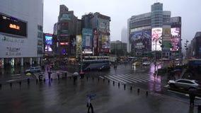 Tráfico y gente que caminan en paso de peatones con lluvia el caer en Ximending en Taipei, Taiwán almacen de metraje de vídeo