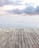 Trä däcka, och blåtthavet med vinkar och den molniga skyen Royaltyfri Fotografi