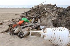 trä med smuts och stycken av plast- samlade på stranden vid t Royaltyfri Foto