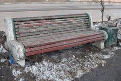 Trä parkera bänkanseendet i gatan, målarfärg som framme skalar av bänken, där ` s en packad snö för grå färger Stå bredvid lien Royaltyfria Foton