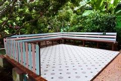 Trä parkera bänken i trädgården Arkivfoton