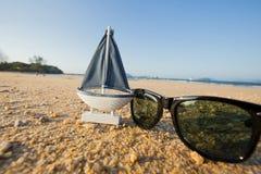 trä segla skeppleksakmodellen och solglasögon i havssanden Royaltyfri Fotografi