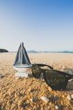 trä segla skeppleksakmodellen och solglasögon i havssanden Fotografering för Bildbyråer