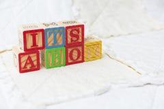 Träalfabetkvarter på att stava för täcke som är dess en metad pojke arkivbilder
