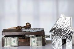 Träask mycket med USA 100 dollar och ett metalliskt hus på tabl arkivfoto