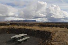 Träbänk bredvid en härlig bergpanorama i Island Royaltyfria Bilder
