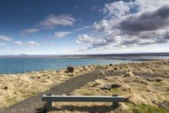Träbänk bredvid en härlig kustlinje i Island Arkivbilder