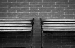 Träbänk för tomma par på grå bakgrund för tegelstenvägg Ensamt och melankoliskt sinnesrörelsebegrepp Bakgrund för ledset, sorg royaltyfria foton