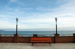 Träbänk framme av havet Arkivfoto