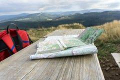 Träbänk med att fotvandra översikter och ryggsäcken Royaltyfri Bild