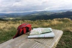 Träbänk med att fotvandra översikter och ryggsäcken Arkivfoto
