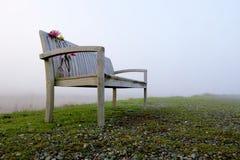 Träbänk med snittblommor utanför på dimmig dag Arkivbild