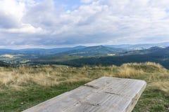 Träbänk- och berglandskap i bakgrund Royaltyfria Foton