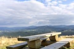 Träbänk- och berglandskap i bakgrund Royaltyfria Bilder