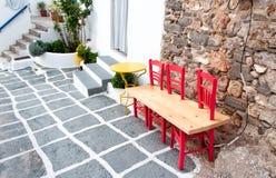 Träbänk på den smala gatan i Naussa, Paros Royaltyfri Bild