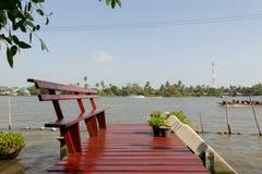 Träbänk på den tropiska flodstranden Arkivbilder