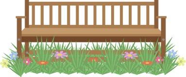 Träbänk på gräsmattan med blommor Arkivfoton