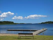 Träbänk på kusten av Bia-Karen sjön i Stockholm royaltyfria bilder