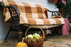 Träbänk som täckas med en filt, korg med äpplen på förgrunden royaltyfria foton