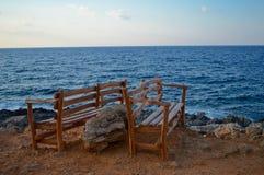 Träbänkar i överkanten av vaggar, med det blåa havet i bakgrunden i Kreta, Grekland Royaltyfri Fotografi