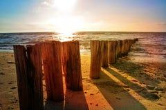 Träbänkar på Nordsjön sätter på land på solnedgången arkivbild